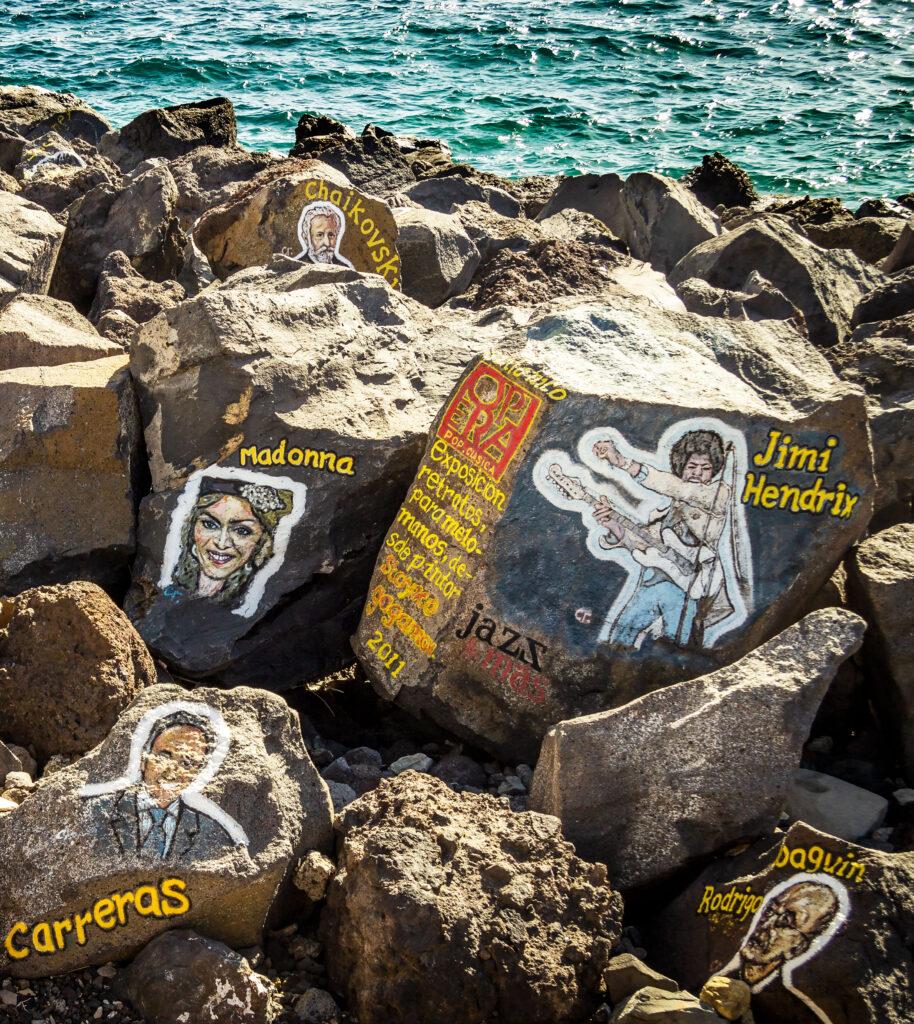 Til de spændende kulturoplevelser på Tenerife hører stenene med kunstnernavne og ansigter ved Tenerifes Auditorium.
