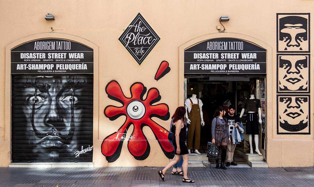 Gadekunsten pryder også Sohos butiksfacader, bl.a. skaterbutikken The Place Sohoi gaden Córdoba. Her er bl.a. værker af Spaniens mest berømte grafittikunstner, SUSO33, (i midten) og OBEY (th).